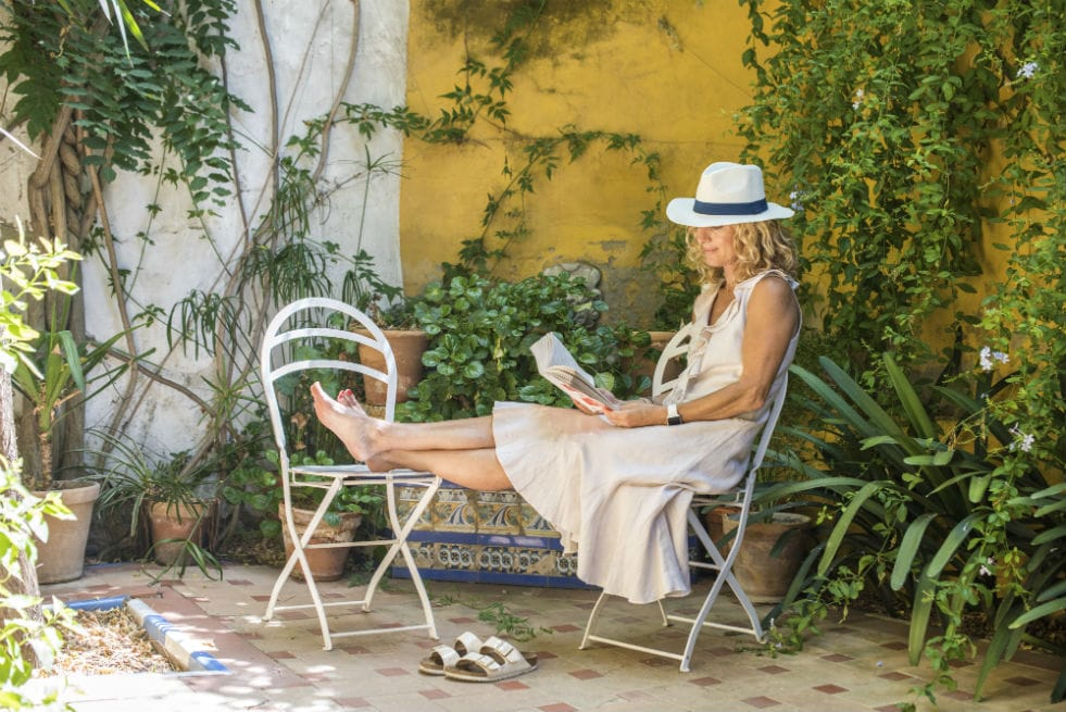 A woman sat on a chair reading a book in Seville.