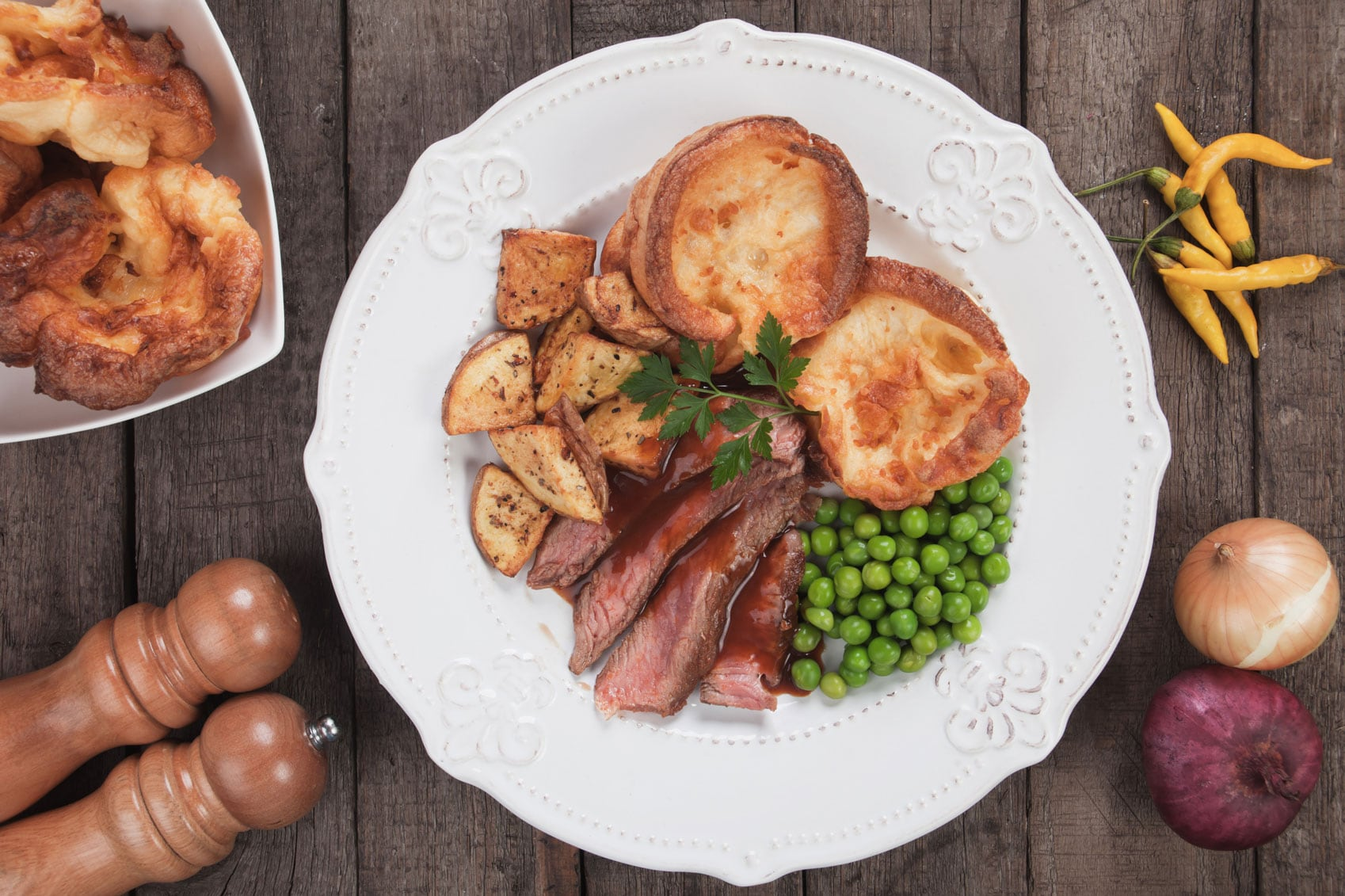 A plate of roast beef, yorkshire puddings, vegetables and gravy