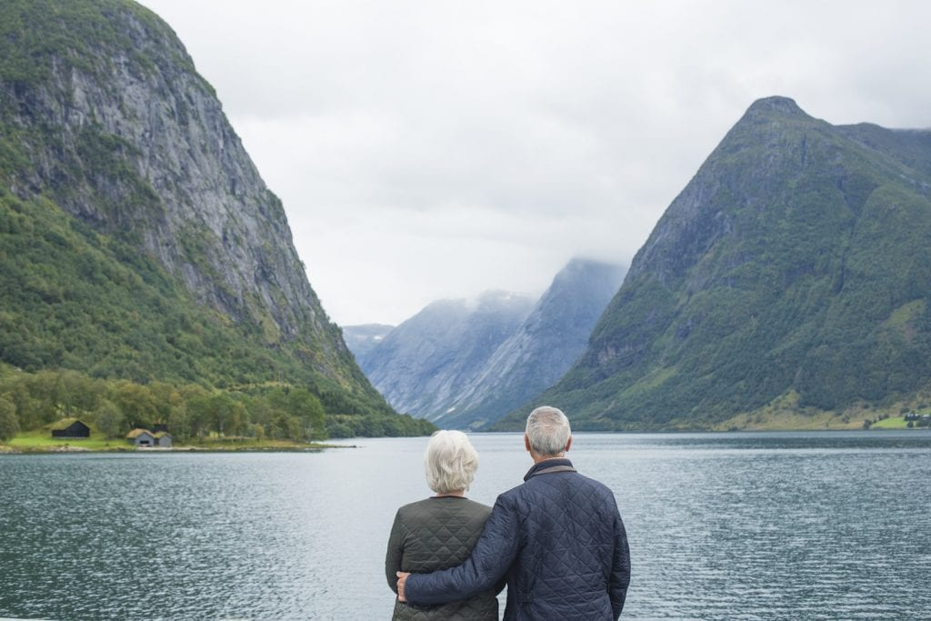 older couple standing with arms around each other by lake in Norway