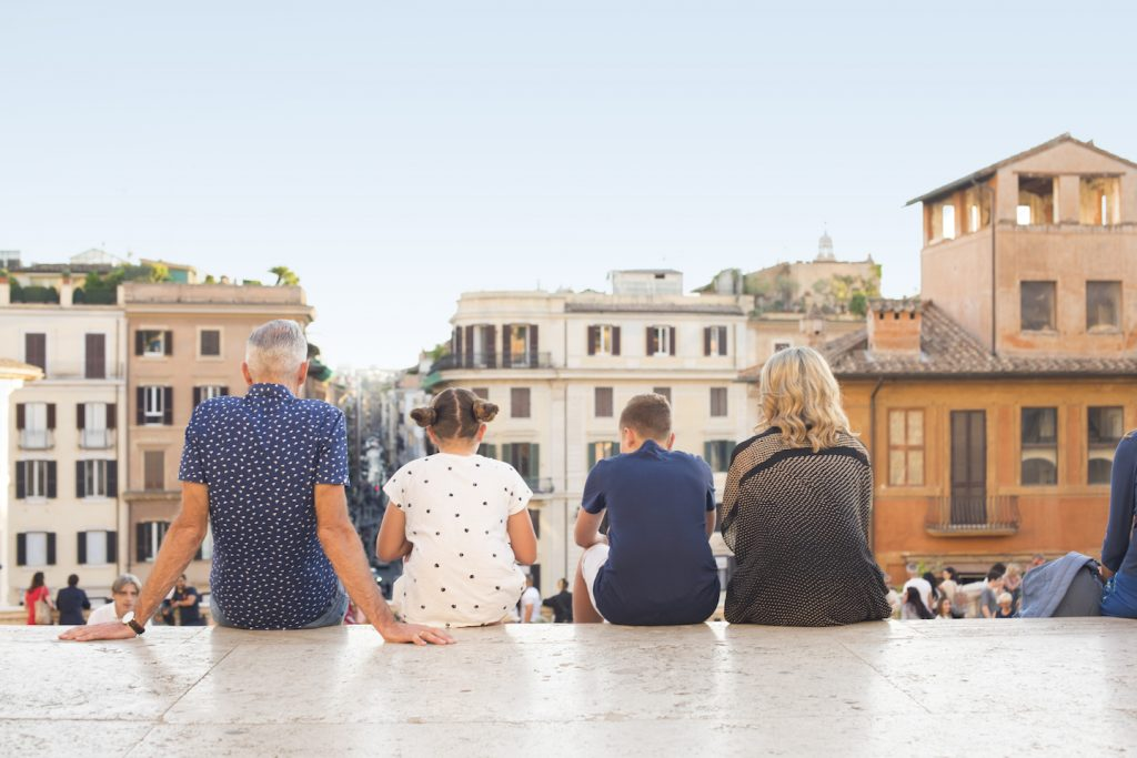 family of four sitting on steps in rome