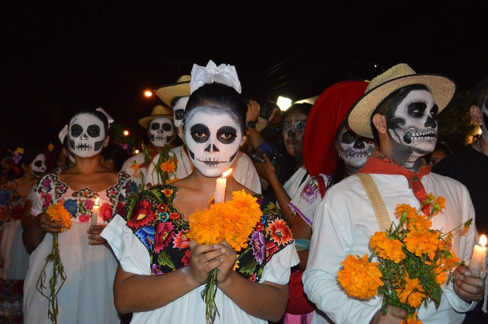 day of the dead parade with traditional makeup and costumes