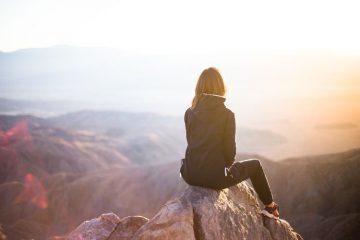 woman watching sunrise over mountain