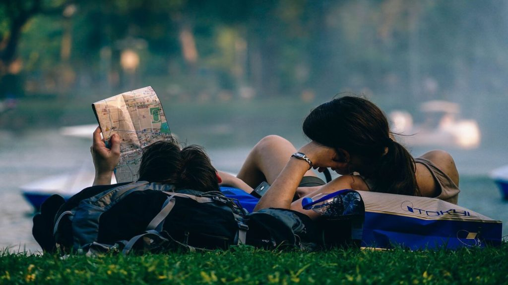 couple reading map in park travel safety