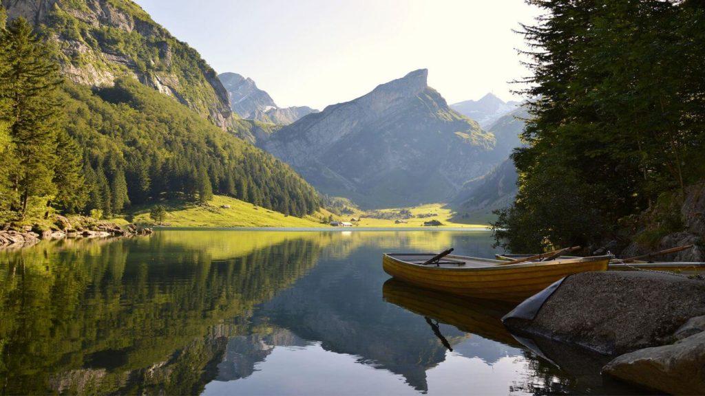 row boat on lake mountains switzerland