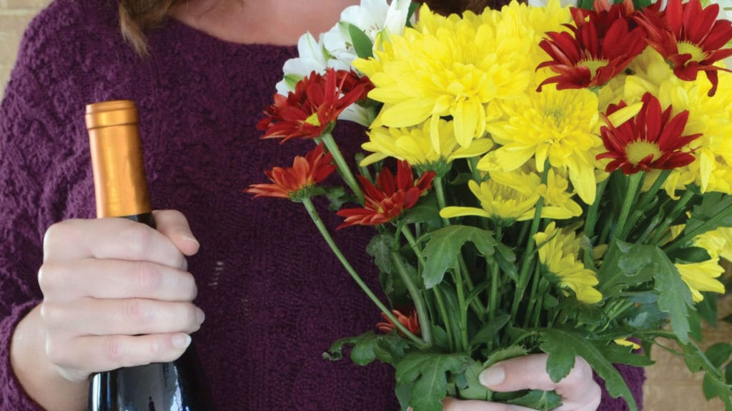 Person holding a bottle of wine and flowers