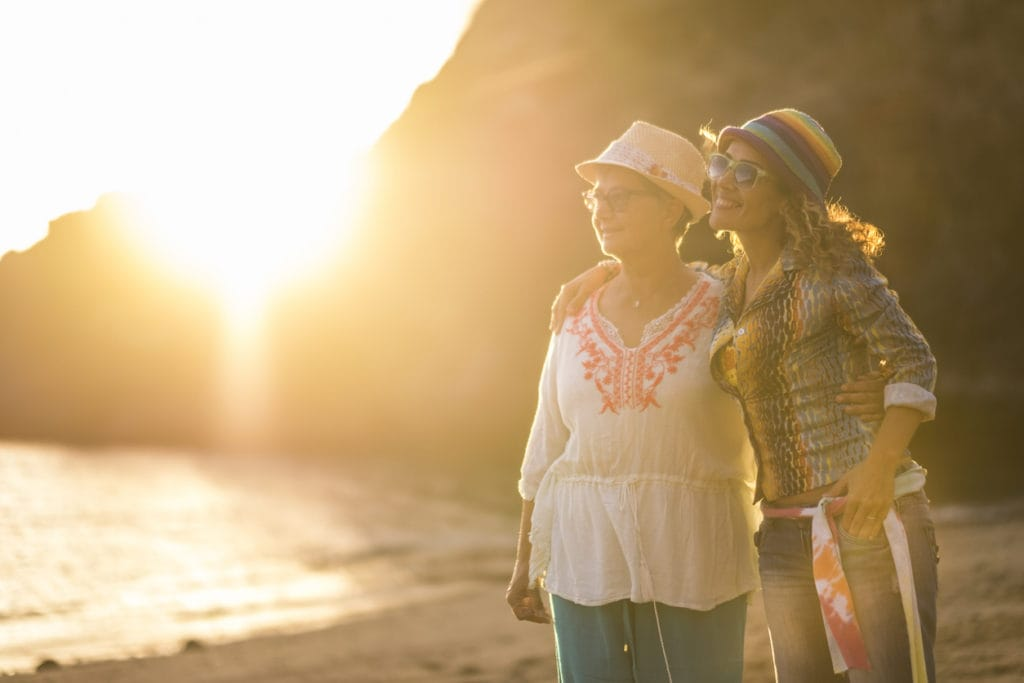 Mother and daughter caucasian people friends at the beach hugging and having fun smiling with golden sun in backlight and ocean in background - family and mixed diversity generations concept
