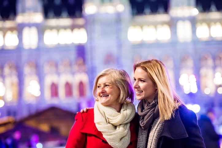 Two beautiful women, mother and daughter in winter clothes on a walk in illuminated night city. Historical building. Vienna, Austria. Travel with your mum