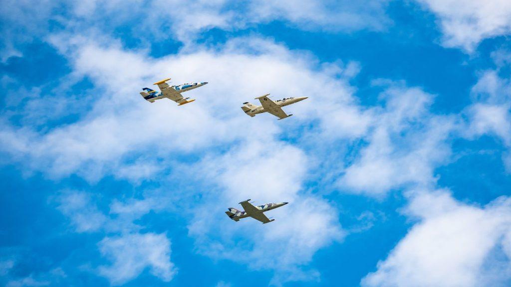 three supersonic planes flying blue skies