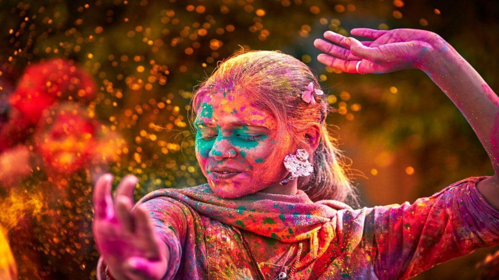 woman dancing colourful powder holi festival india