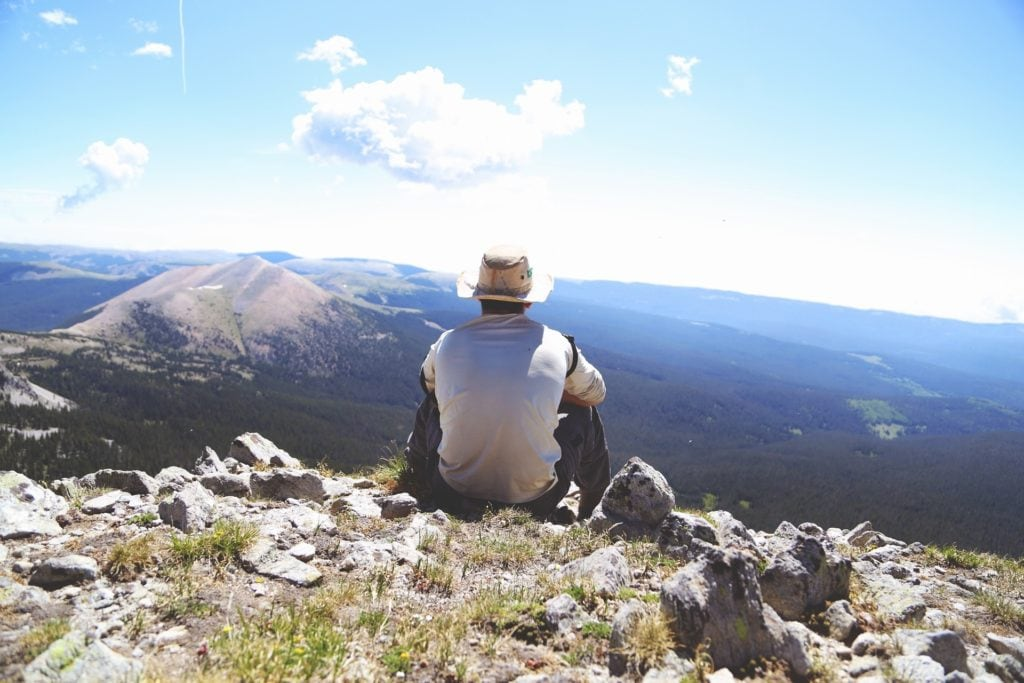 man looking out at view of mountains