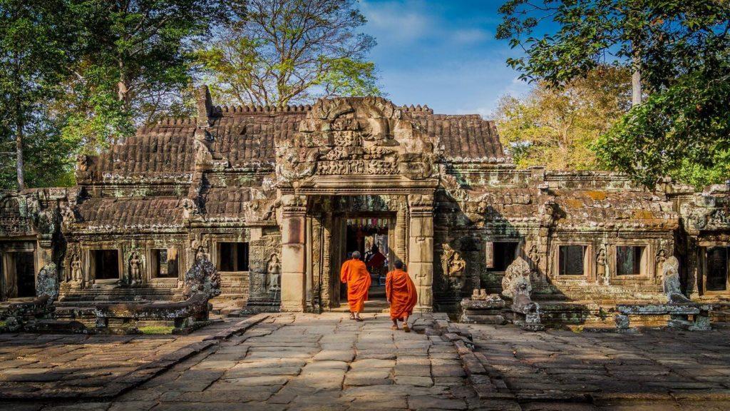orange robed monks ancient ruins Angkor Wat Cambodia