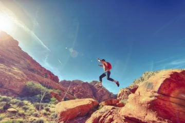 man jumping over rocks