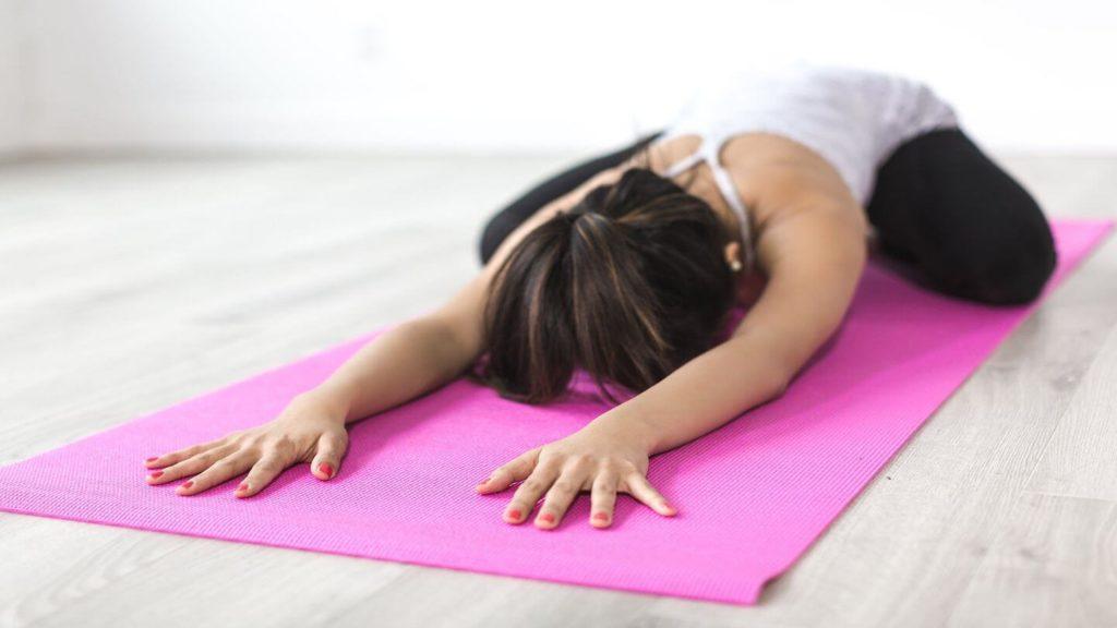 woman stretching pink yoga mat