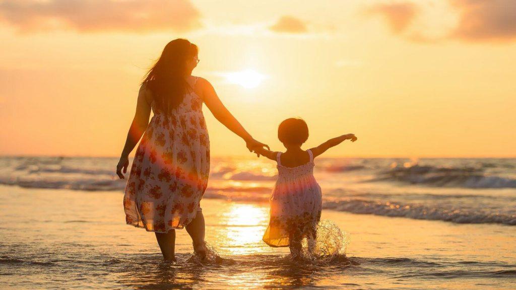 adult and child splashing waves beach