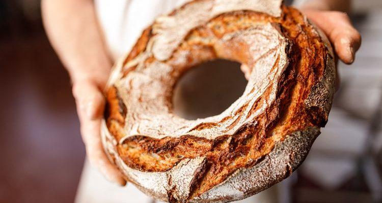 baker holding round bread loaf