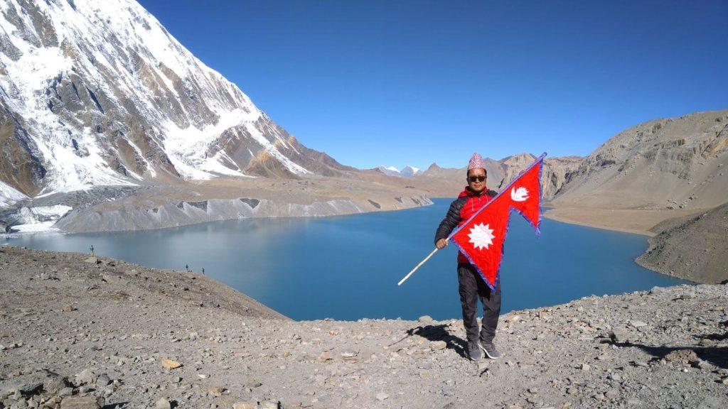 man holding Nepal flag blue lake Himalayas