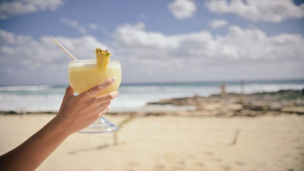 hand holding pina colada on beach