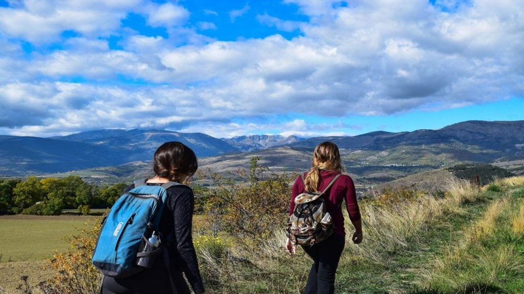 two people hiking mountain walking trail