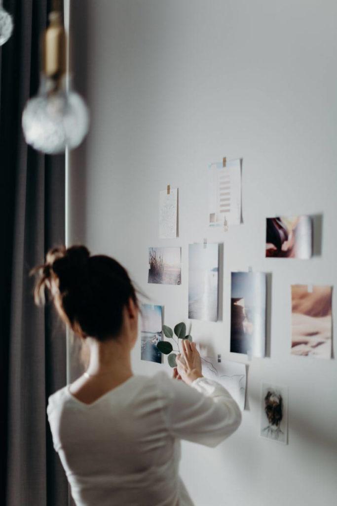 woman hanging photos souvenir collection