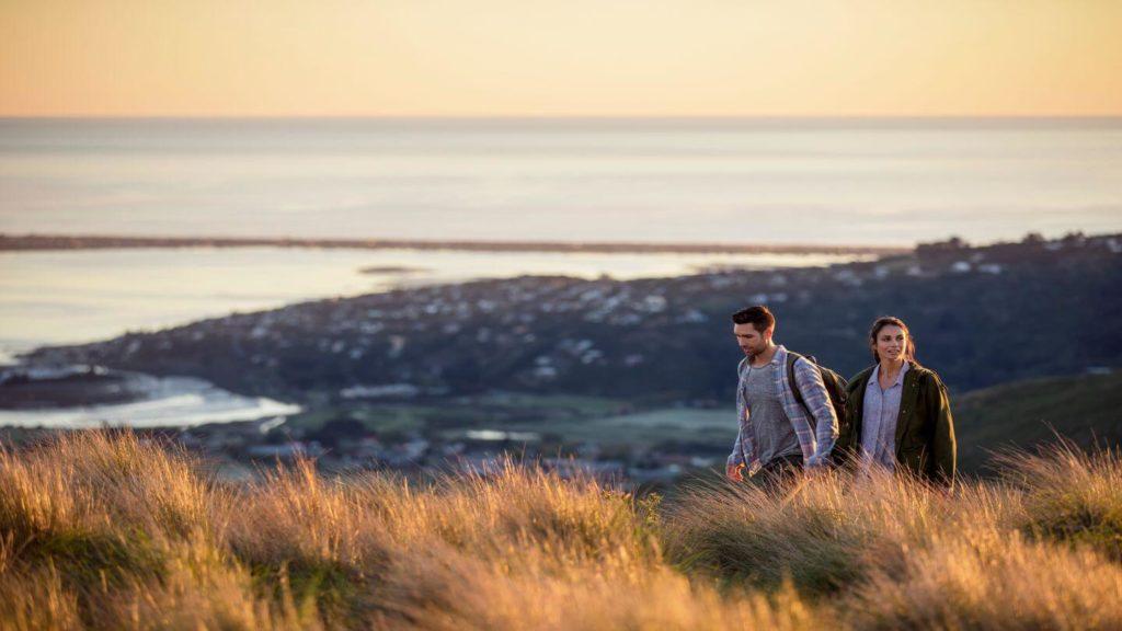couple walking through Port Hills Christchurch New Zealand