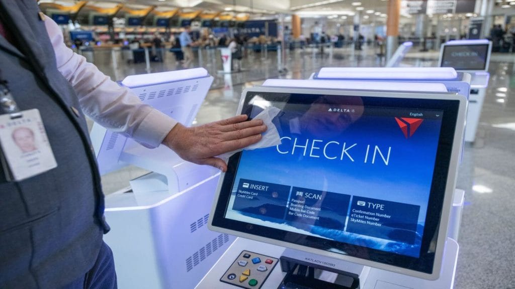 Delta staff wiping down check in kiosks at airport how do airlines clean the plane
