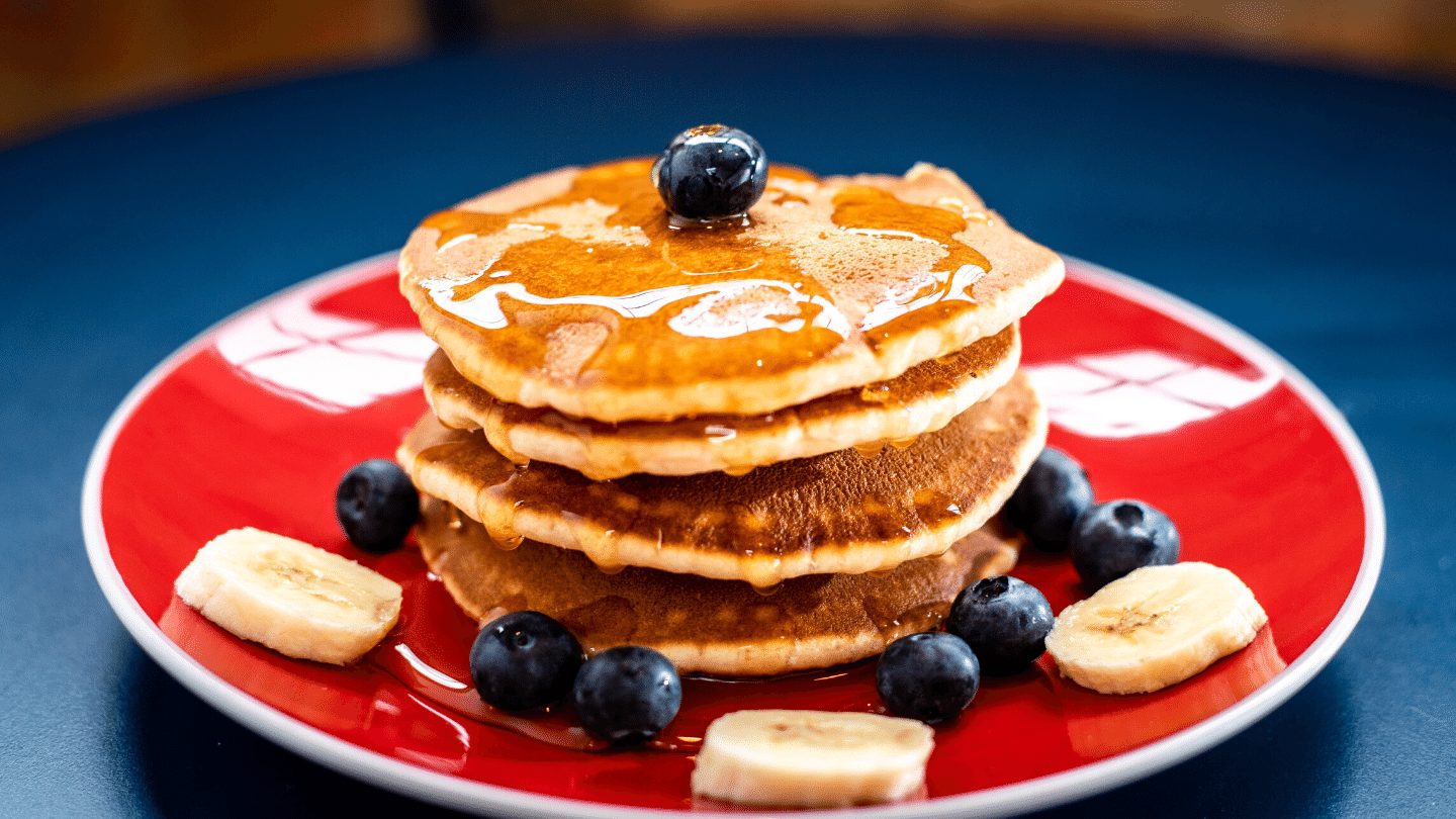 Maple syrup poured over Pancakes with blueberries and banana