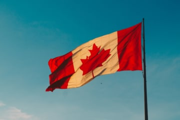 Canada flag in front of blue sky