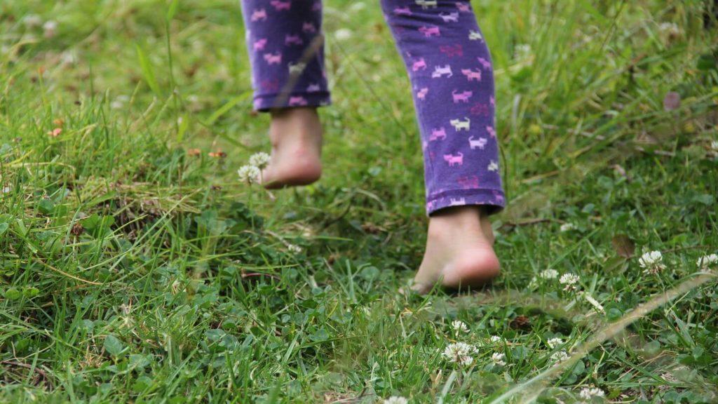 child running barefoot through grass