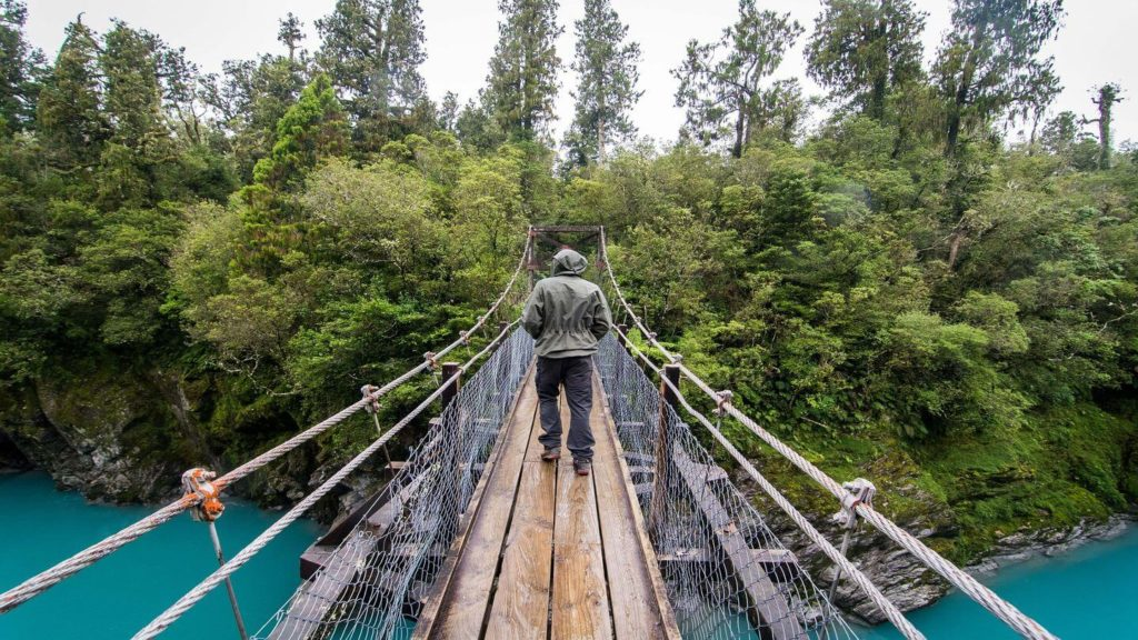 person walking along suspension bridge over blue river