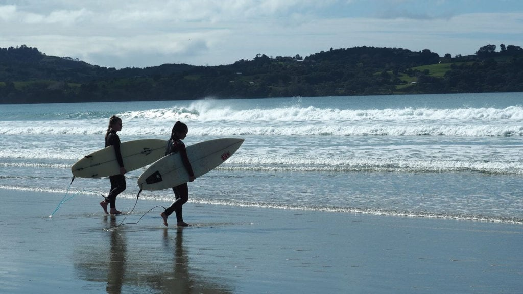 two surfers at the beach new zealand laidback lifestyle
