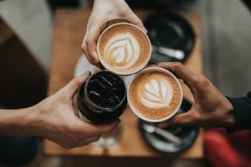 hands holding three coffees