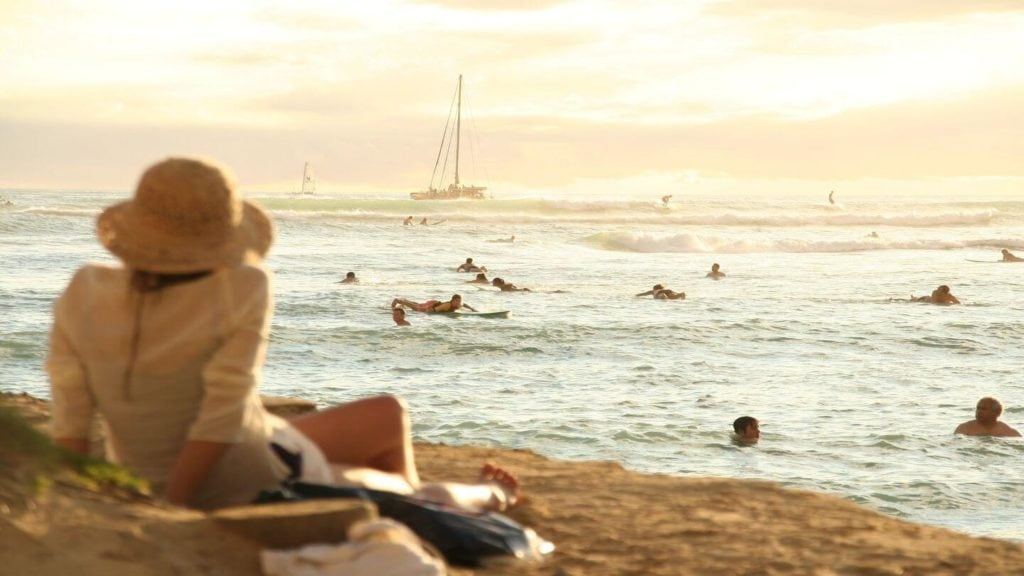 adult sitting on beach people swimming at sunset Hawaii