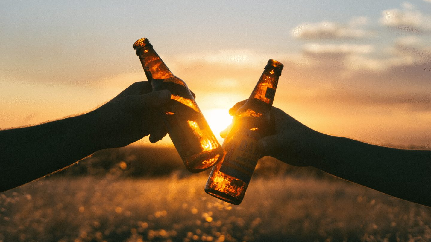 Hands holding two beer bottles at sunset