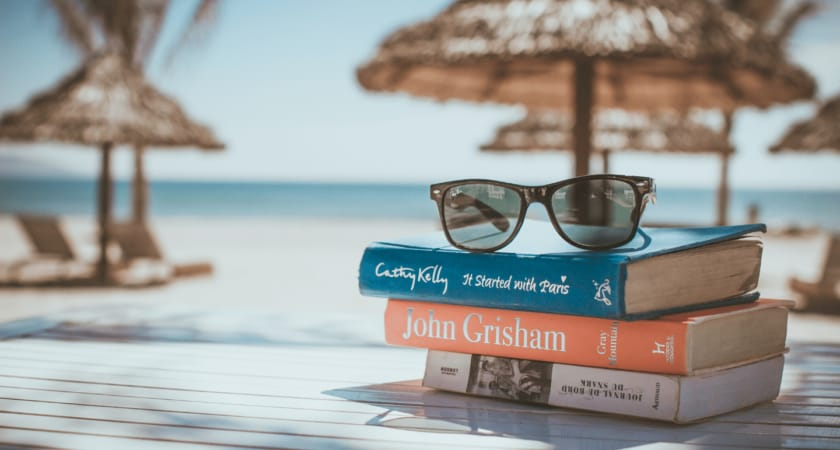 A pile of books at the beach with sunglasses on top