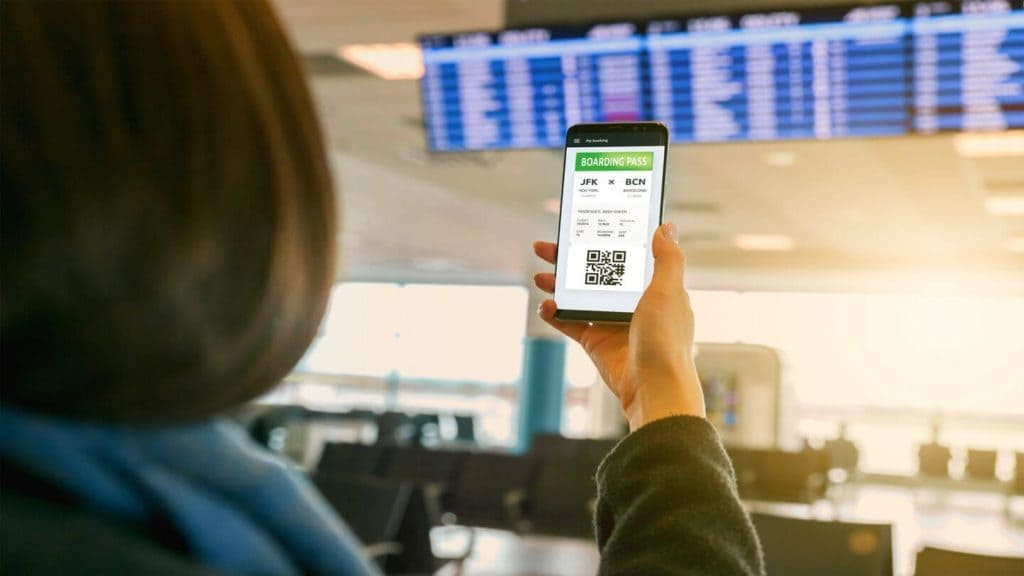 adult holding smartphone with digital boarding pass at an airport