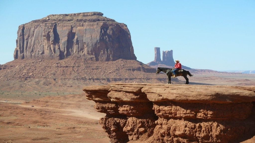 man riding horse among sandstone towers of Monument Valley USA