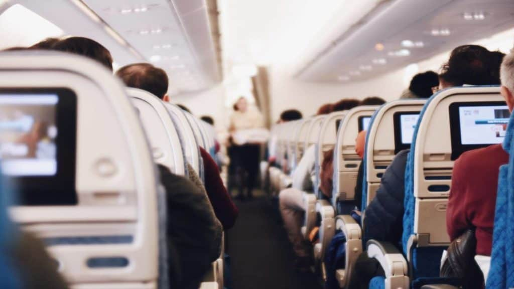 passengers sitting in airplane seats COVID-19 travel questions