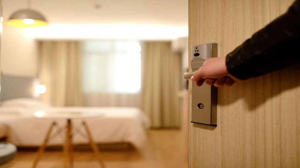 hand opening door to hotel room