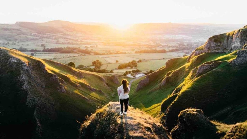 woman standing on mountain viewpoint overlooking green fields