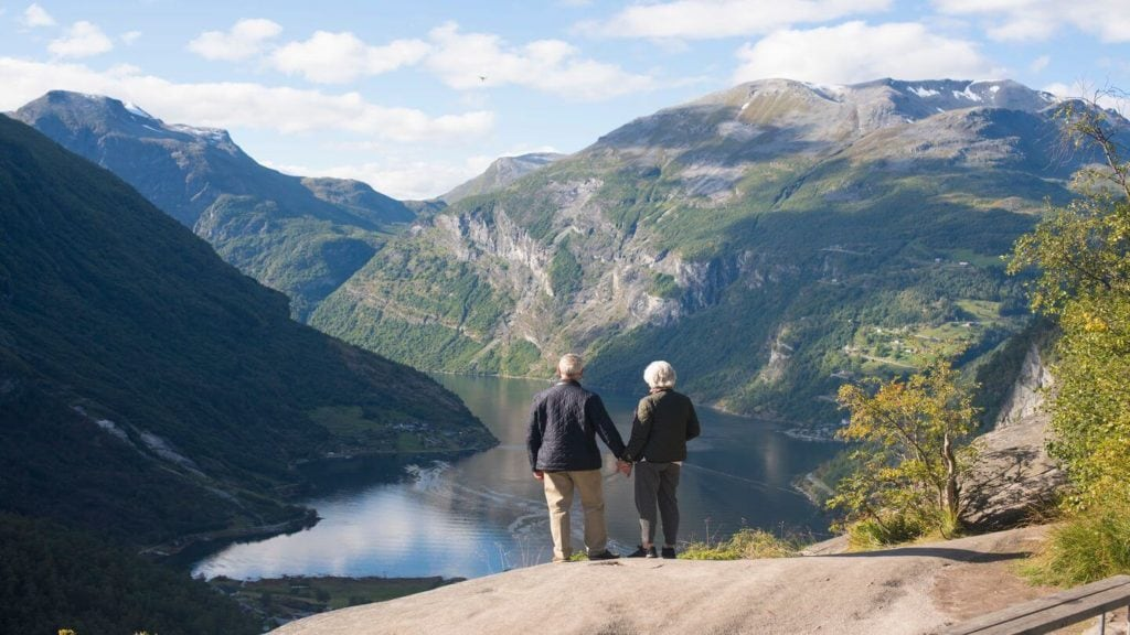 couple holding hands on a mountain fjord viewpoint