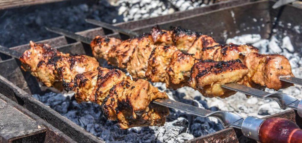 meat skewers grilling over hot coals
