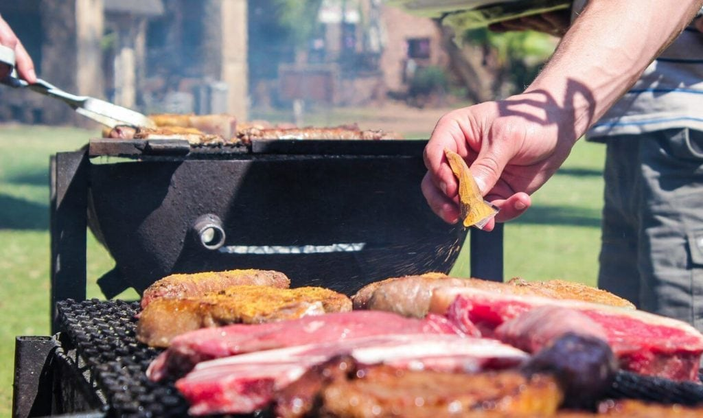 adult seasoning meat on a grill South African braai