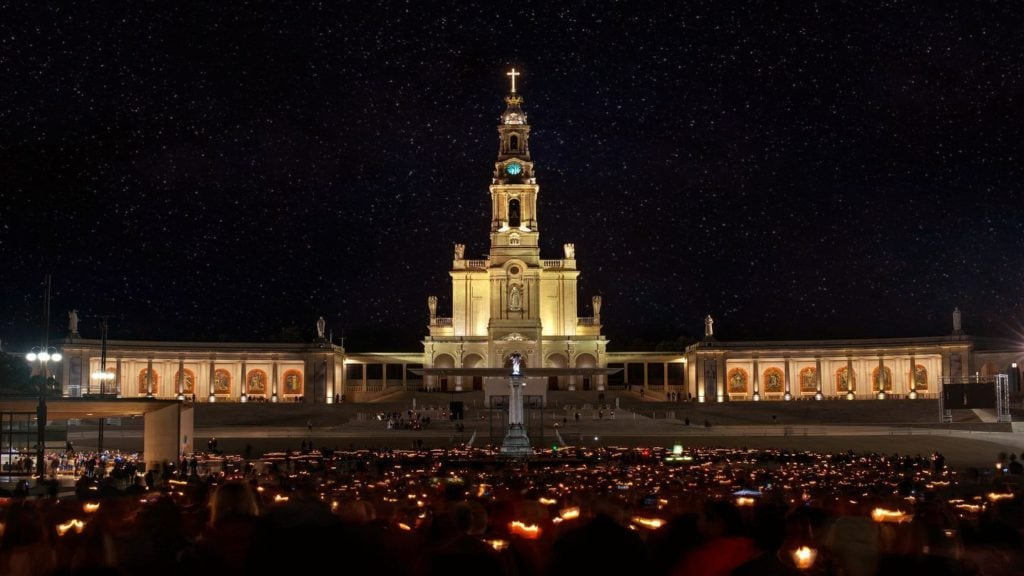 Sanctuary of Fatima worshippers holding candles at night Portugal