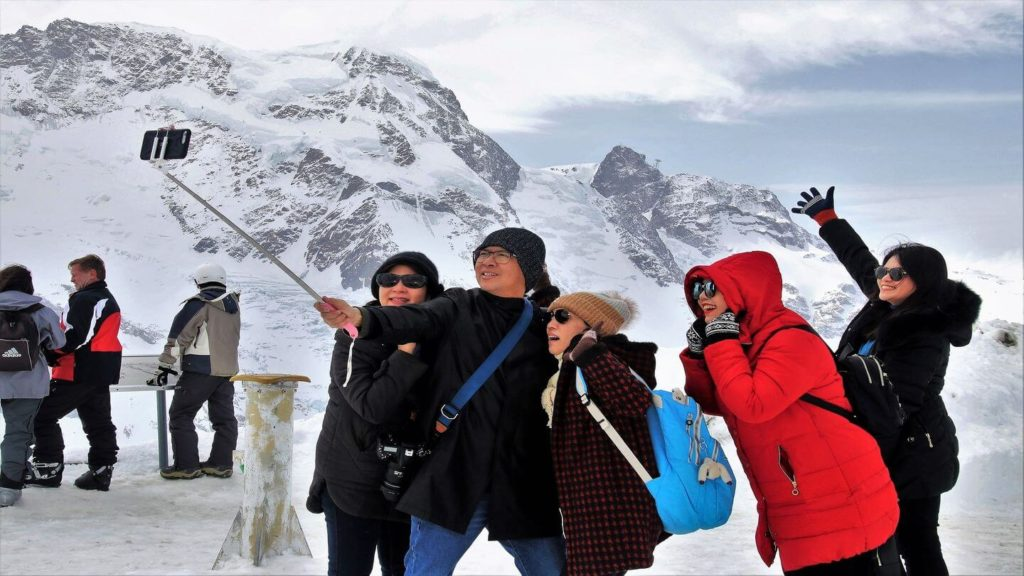 travellers taking a group photo at the snow