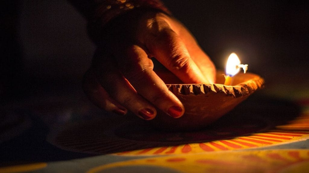 hand lighting a candle for Diwali celebrations