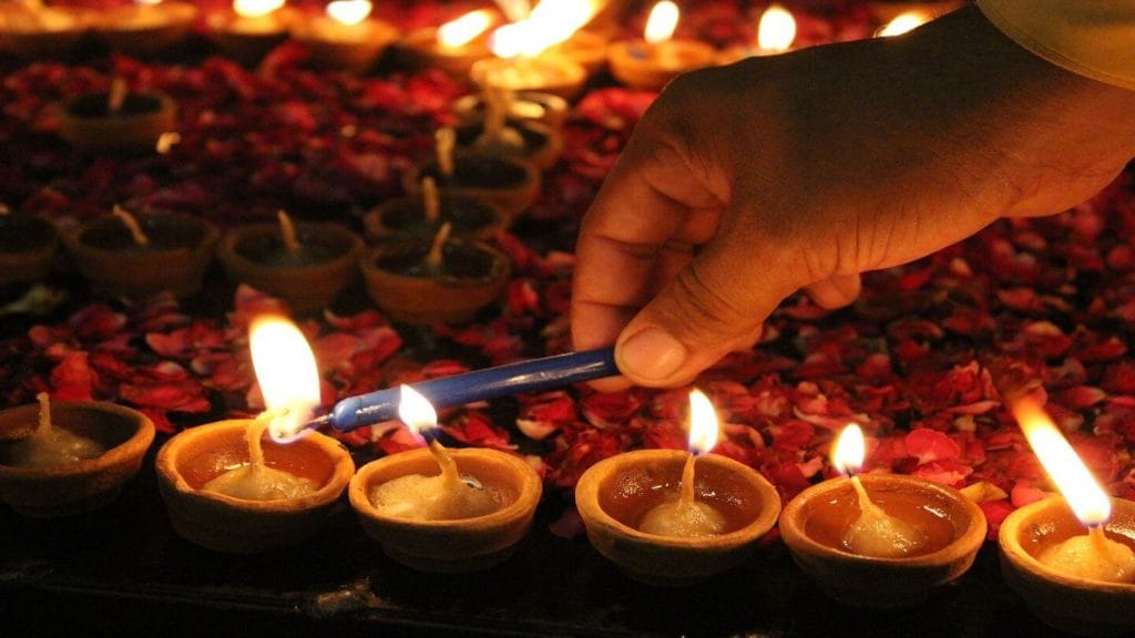 A hand lighting candles for Diwali