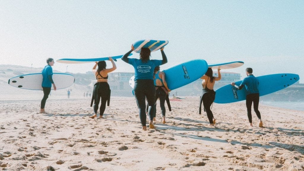 group of people learning to surf on the beach
