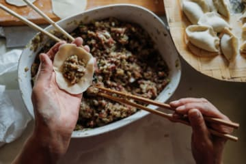 hands stuffing a dumpling with chopsticks - chinese dining experience