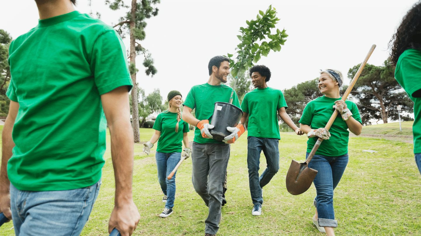Group of people in green t-shirts planting trees - responsible travel