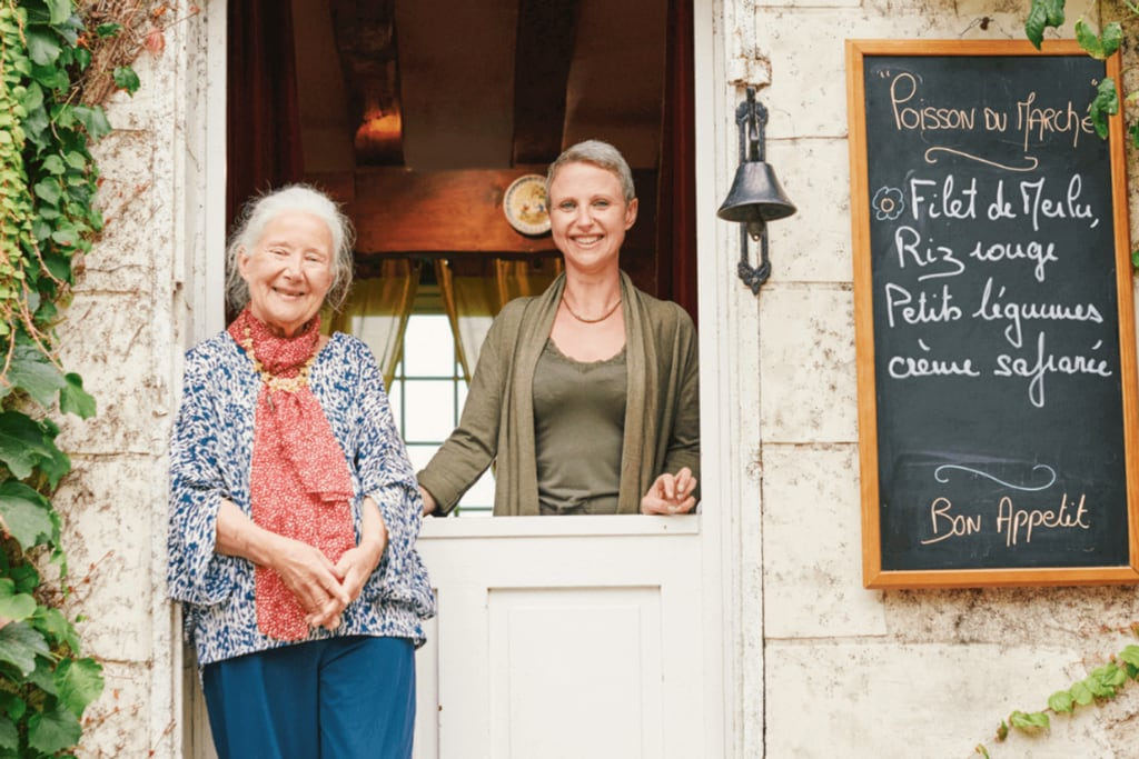two women at their restaurant in France dining with strangers